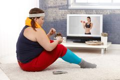 Fat woman eating chocolate cake in sportswear. Fat women sitting on floor with chocolate cake while watching fitness program on television Royalty Free Stock Photos