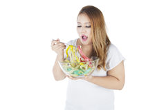 Fat woman eating measuring tapes. Portrait of fat woman eating measuring tapes, concept of diet, isolated on white background Royalty Free Stock Images