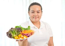 Fat woman eating salad Stock Images