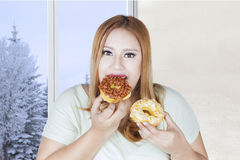 Fat woman eating two donuts Royalty Free Stock Photography