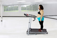 Fat woman exercising with a treadmill royalty free stock photo