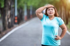 Fat woman feeling tired while running in the park. Exercise and healthy concept : Fat woman feeling tired while running in the park royalty free stock photography