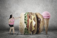 Fat woman fighting with junk foods. Image of fat woman wearing sportswear while fighting with junk foods. Diet concept Stock Image