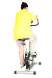Fat woman on  fitness bicycle Royalty Free Stock Photos
