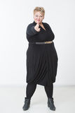 Fat woman with a gun. in a black dress Stock Images