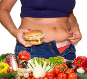 Fat woman with hamburger and vegetables Royalty Free Stock Images
