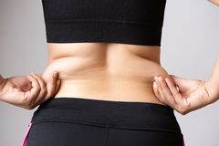 Fat woman hand holding excessive belly fat. Healthcare and woman diet lifestyle concept to reduce belly and shape up healthy