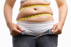 Fat woman holding her unzip jeans. With measuring tape around her belly, a concept to get a diet Stock Photos
