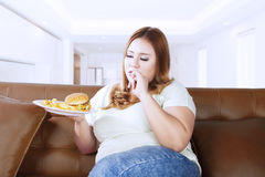 Fat woman holding junk food on the couch Stock Images