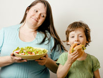 Fat Woman Holding Salad And Little Cute Boy With Hamburger Stock Photo