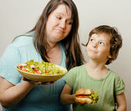 Fat Woman Holding Salad And Little Cute Boy With Hamburger Stock Image