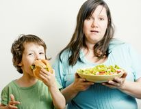 Fat Woman Holding Salad And Little Cute Boy With Hamburger Teasing, Real Family On White Eating Food Stock Images