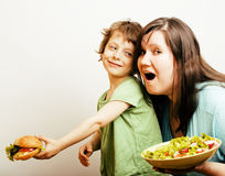 Fat woman holding salad and little cute boy with hamburger on white background Royalty Free Stock Photo