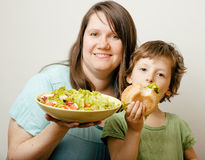 Fat woman holding salad and little cute boy with hamburger Royalty Free Stock Photography