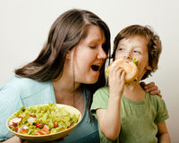 Fat woman holding salad and little cute boy with Royalty Free Stock Photo