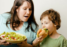 Fat woman holding salad and little cute boy with. Fat women holding salad and little cute boy with hamburger teasing real family royalty free stock image
