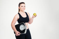 Fat woman holding weighing machine and apple Royalty Free Stock Images