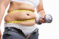Fat woman holding weight to exercise royalty free stock image