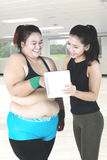 Fat woman and instructor smiling at digital tablet. Fat women and young instructor smiling together while looking at digital tablet in fitness center Stock Photo