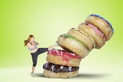 Fat woman kicking a pile of donuts. Picture of fat woman refusing to eat sweet food by kicking a pile of donuts. Shot with green screen background stock images