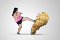 Fat woman kicks fried chicken thigh on studio stock image