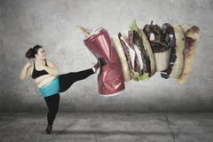 Fat woman kicks soft drink and junk foods. Fat young woman kicking a can of soft drink and junk foods while wearing sportswear Royalty Free Stock Photos