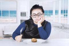 Fat woman looking boiled potato Stock Images
