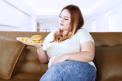 Fat woman looking at food on the couch Royalty Free Stock Image