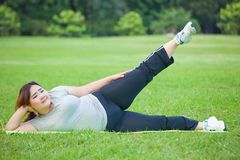 Fat woman lying by exercise leg upwards Royalty Free Stock Photos