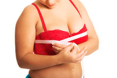 Fat woman measuring breast. In underwear royalty free stock image