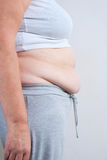Fat woman. Pinching her fat tummy Royalty Free Stock Image