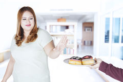 Fat woman refuses donuts from someone. Portrait of fat woman refuses donuts offered someone while standing at home royalty free stock image