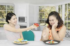 Fat woman rejecting to eat donuts at home. Picture of fat women eating salad and refuse to eat donuts from her friend while sitting at home Royalty Free Stock Image