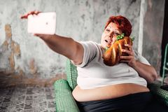 Fat woman with sandwich in hand makes selfie. Laziness and obesity, overweight people. Unhealthy lifestyle, fatty female Stock Photography