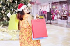 Fat woman in Santa hat with shopping bags Royalty Free Stock Image