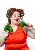 Fat woman with sensuality red lipstick in curlers on a diet holding parsley and dill. To eat isolated on the white background Stock Photo