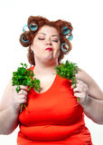 Fat woman with sensuality red lipstick in curlers on a diet holding parsley and dill. To eat isolated on the white background Stock Image