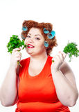 Fat woman with sensuality red lipstick in curlers on a diet holding parsley and dill. To eat isolated on the white background Stock Photos