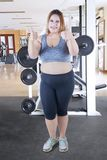 Fat woman shows thumbs up in gym center. Portrait of young fat woman showing thumbs up at the camera while standing in the gym center Stock Photo