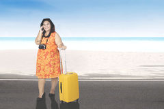 Fat woman with smartphone on the beach Royalty Free Stock Photography