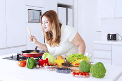 Fat woman sniffing meal on frying pan Royalty Free Stock Photos
