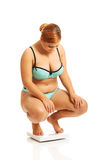 Fat woman squats on scale Stock Images