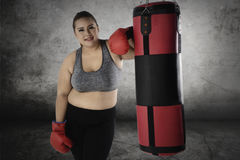 Fat woman standing near a boxing sack. Picture of beautiful woman with big body while standing near a boxing sack after doing exercise Stock Images