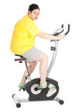 Fat woman on stationary fitness bicycle Royalty Free Stock Photography