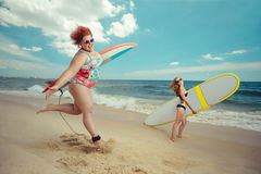 Fat woman with the surfboard. Beautiful young fat women is runing to the summer sea with the surfboard royalty free stock photos