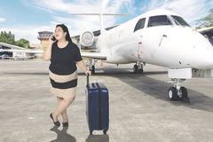 Fat woman talks on the phone in airport Stock Image