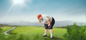 Fat woman tired after run training, overweight. Green field and cityscape on background. Burning of calories. Female obesity Stock Photos