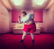 Fat woman on training, fight against obesity. Fat woman on training with dumbbells, fight against obesity, overweight problem. Fastfood eating Stock Image