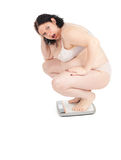Fat woman in underwear on scale. Squats on scale young fat woman in underwear, series royalty free stock photos