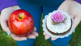 Fat woman wants to lose weight diet top view in blue suit on green grass selects red big apple or round brown with white cake. With rose of pink color holds royalty free stock photos